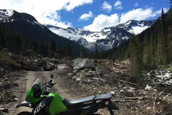 Green Kawasaki motorcycle on a dirt road in front of snow capped mountains