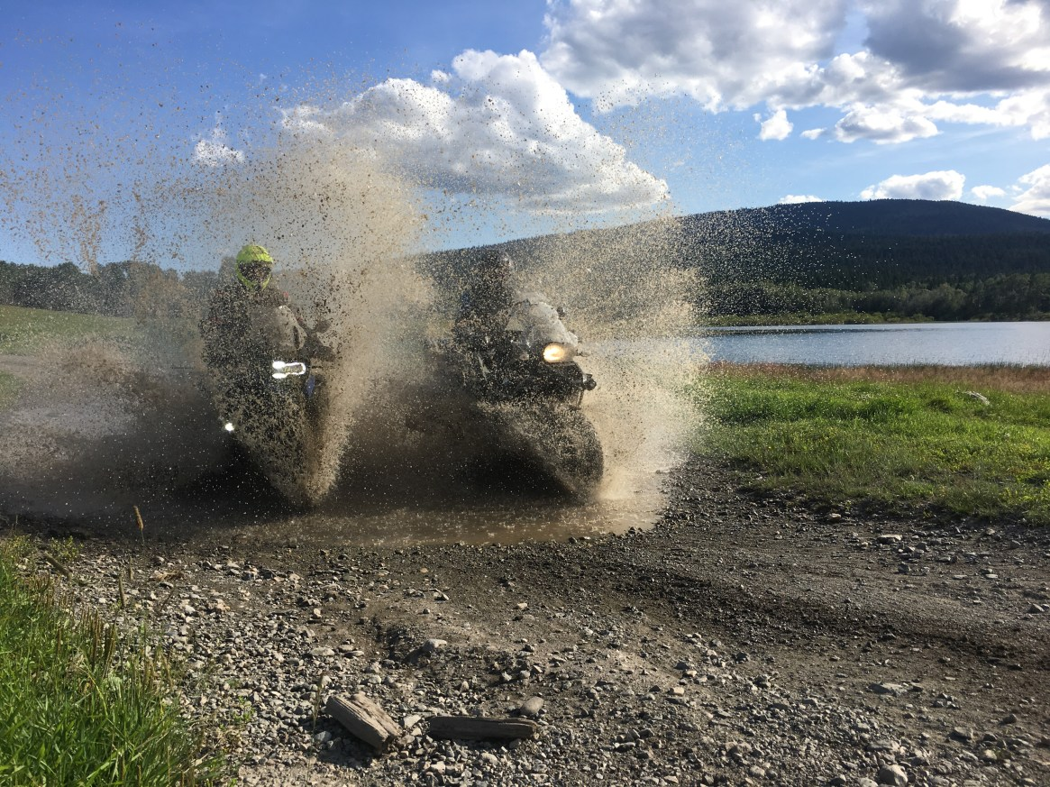 2 BMW GS1200 motorbikes spraying mud on a dirt road outside lillooet