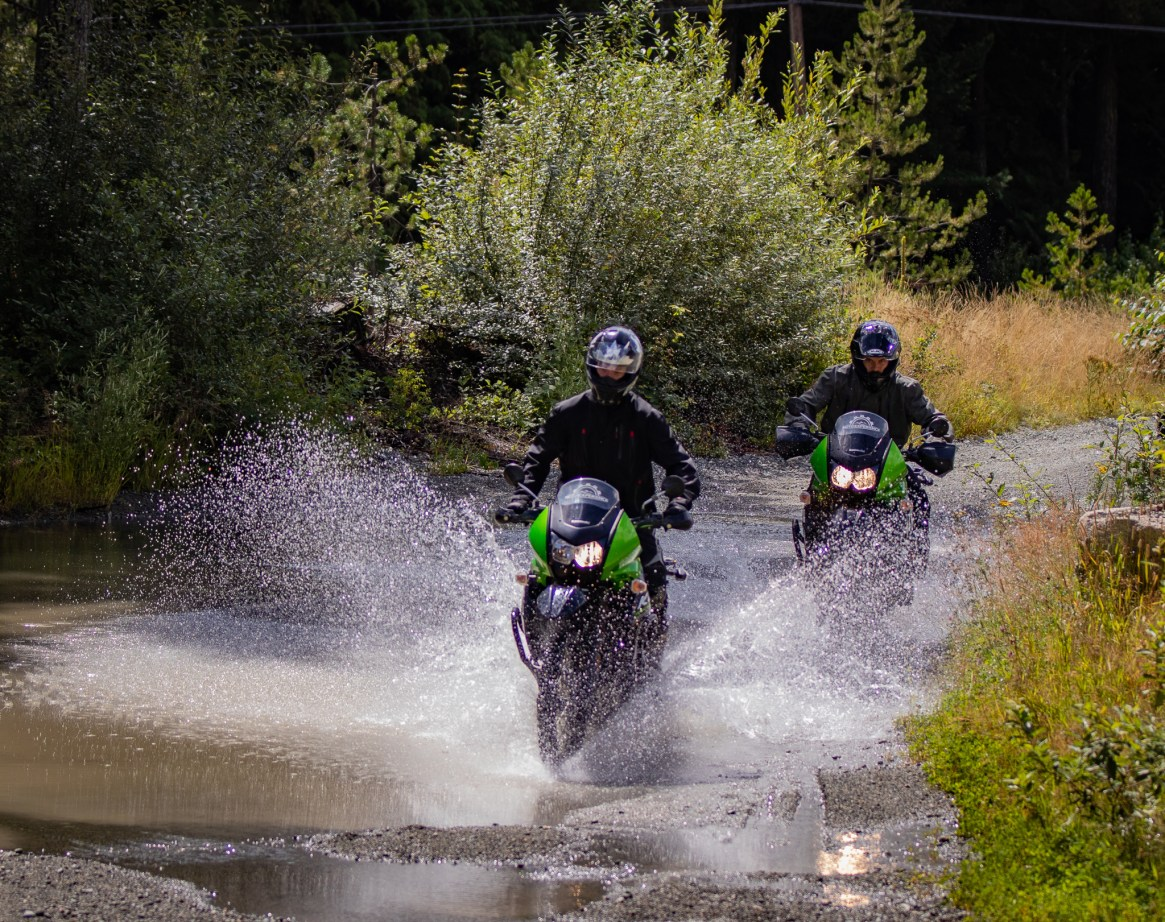 2 KLR650 motorcycles riding through a puddle splashing water