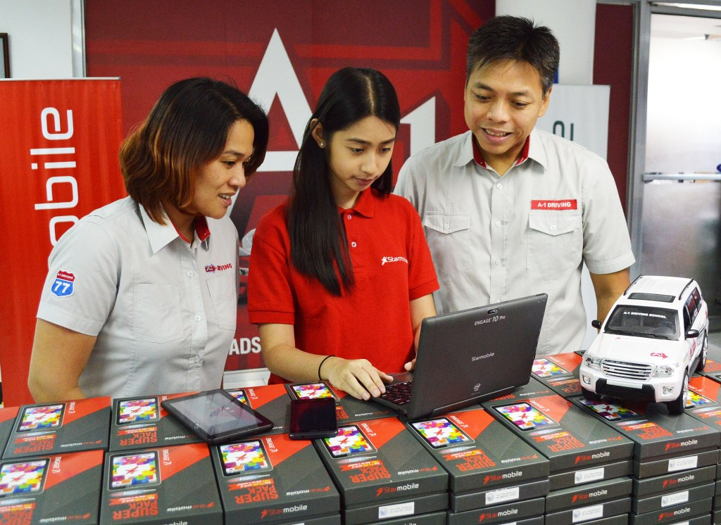 Vikha Vargas of Starmobile Marketing (center) demos the ENGAGE 10 Pro 2-in-1 Windows Tablet, UP Snap Android Smartphone, and ENGAGE 7i Android Tablet to A1 Driving School Business Development Head Luna Garcia (left) and AVP Aljun Garcia (right)