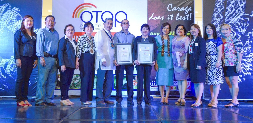 The DTI-Bureau of Domestic Trade Promotion (BDTP) awarded Certificates of Accreditation to the OTOP TindahangPinoy stores in Butuan City. These are operated by the CARAGA Regional Association of Traders & Entrepreneurs in Food, Inc. (CReATE Food Inc.). Receiving the certificates are Kevin Uy, OTOP TindahangPinoy-Butuan operations manager, and Esther Uy, CReATE Food Inc. president (sixth and seventh from left, respectively), with other CReATE Food officers. Presenting the certificates are DTI-BDTP assistant director Marievic Bonoan (fourth from left); DTI-Caraga regional director Brielgo Pagaran (fifth from left); and DTI-Industry Promotions Group undersecretary Nora Terrado (fifth from right).