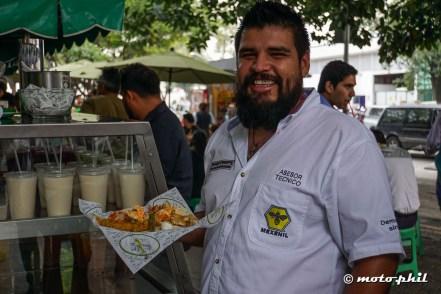 "Mexican man holding ""La Paz"" Tacos"