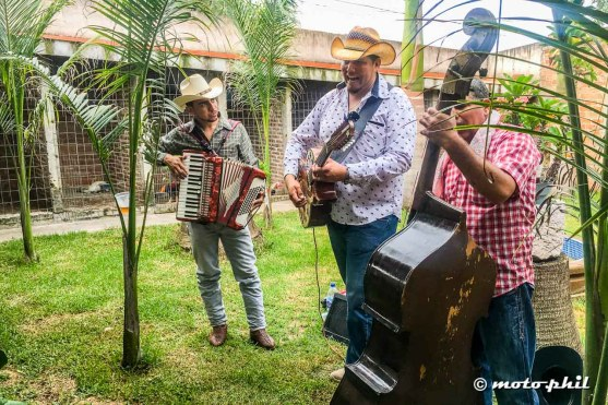 Three mexicans playing their instruments at a private party