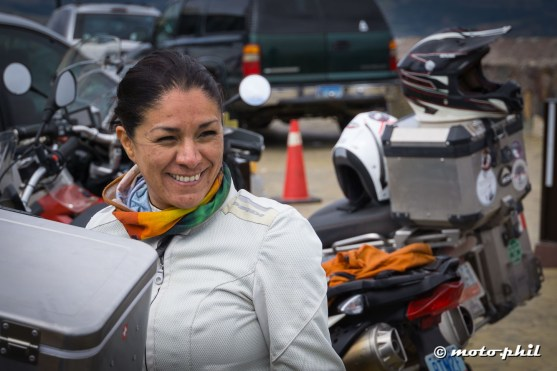 Alejandra Ortiz with white riding gear, colorful scarf in front of motorcycles