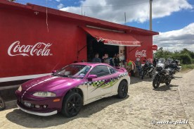 Car painted in racing design in front of shop with Coca Cola sign