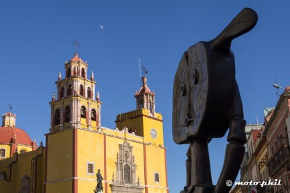 Metal art with yellow church in background