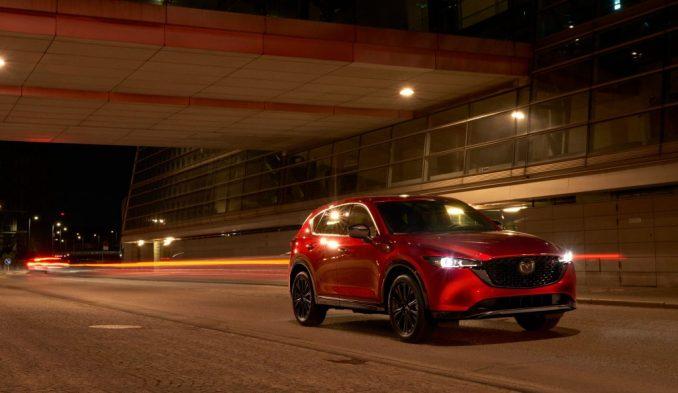سيارة مازدا CX-5 الحمراء لعام 2022 تقود بجوار مبنى كبير في الليل