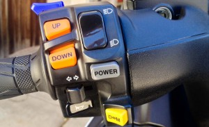"The Burgman's many options are (from top to bottom): mirror fold switch (blue), thumb shifting (orange), power mode switch (gray), and drive/manual ""shift"" mode (yellow)."