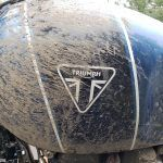 Mud-splattered Triumph Scrambler 1200 XE fuel tank