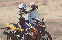 """Editor-in-Chief Plummer (on the CBR600) queries Managing Editor Fortune: """"Where's the first turn, and what's the lap record?"""""""