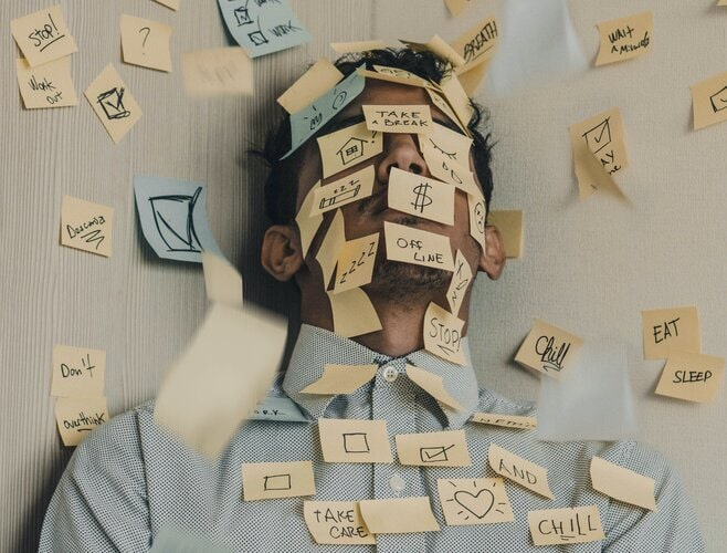 man covered in post it notes - information overload