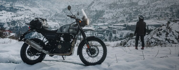 royal enfield and rider in the snow - winter motorcycle gloves