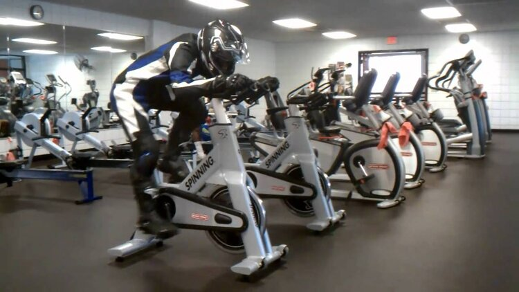 biker in leathers and helmet on spin bike in gym