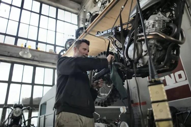 motorcycle mechanic working on bike