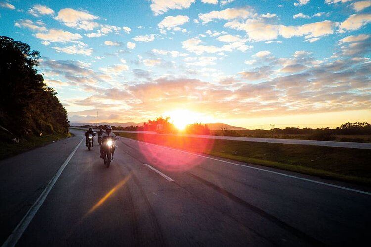 3 bikers on country road at sunrise - long-distance motorcycling