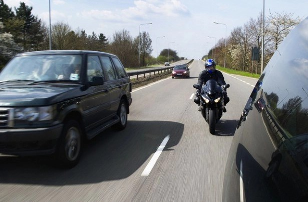 motorcycle between two cars