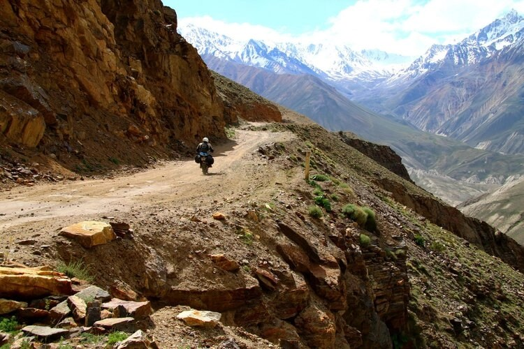 motorcycle on mountain dirt road - cheaper alternatives to adventure bikes