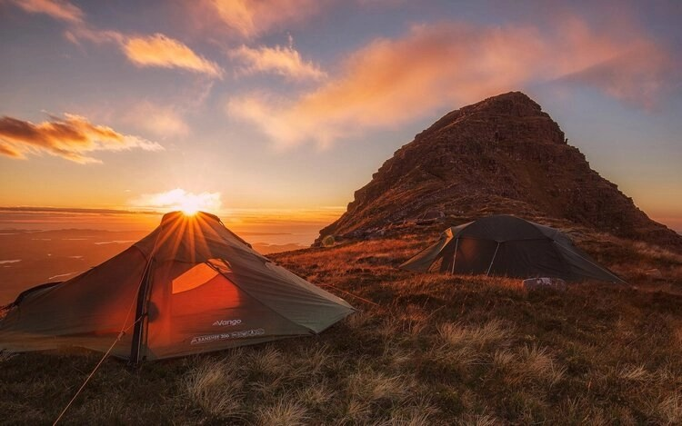 motorcycle tent on cliff top at sunset