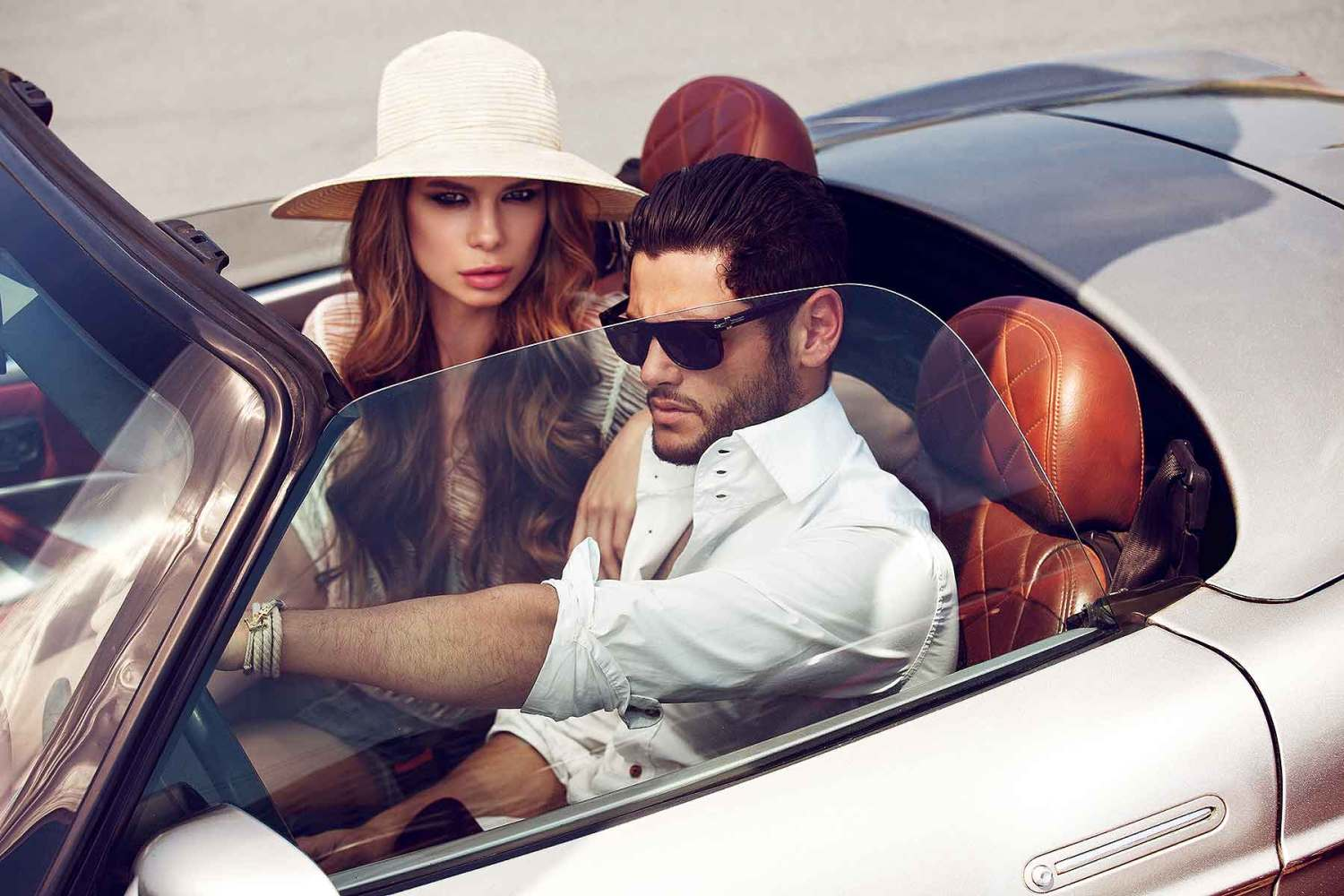A beautiful couple driving a sports car