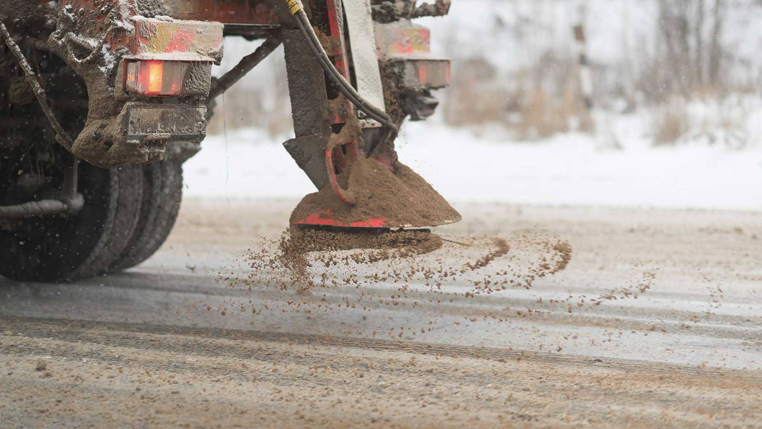 Close-up of a road gritter spreading salt