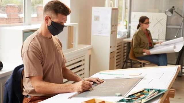 architect wearing mask working at a drafting table in an office setting