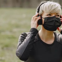 woman exercising out side putting on headphones and wearing a mask