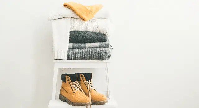 Clean clothing and boots sitting on shelves