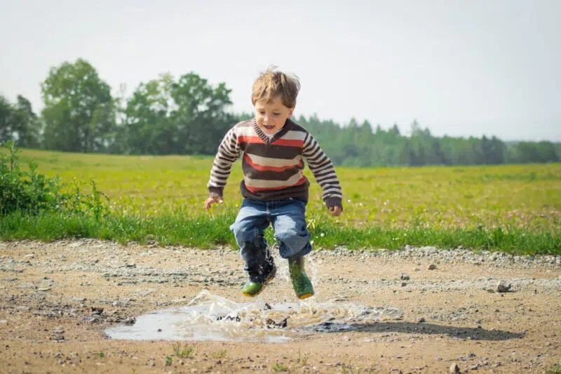 little boy jumping into a mud puddle