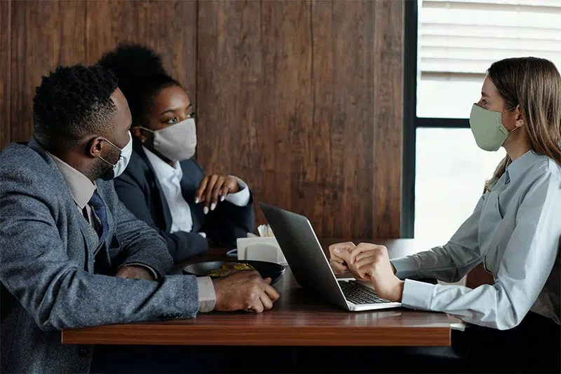 business people wearing masks and talking
