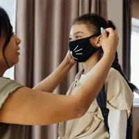 mother putting mask on child