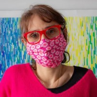 woman standing in front of a colorful background wearing a pink mask and sweater