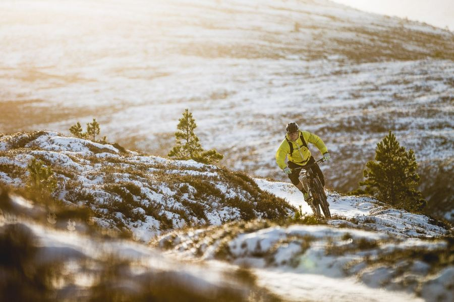 Local Aviemore mountain bike guide Chris Gibbs carving through the snow.