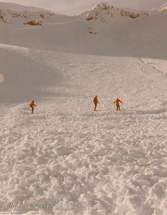 Patrol surveys the debris of a large slide in Glacier Bowl. 1970s.