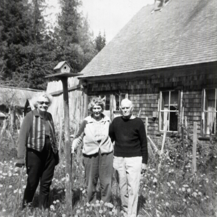 Phil and Dorothy Tapley and Myrtle Philip standing beside a birdhouse in a field of dandelions. The Farmhouse in the background. Courtesy Whistler Museum.