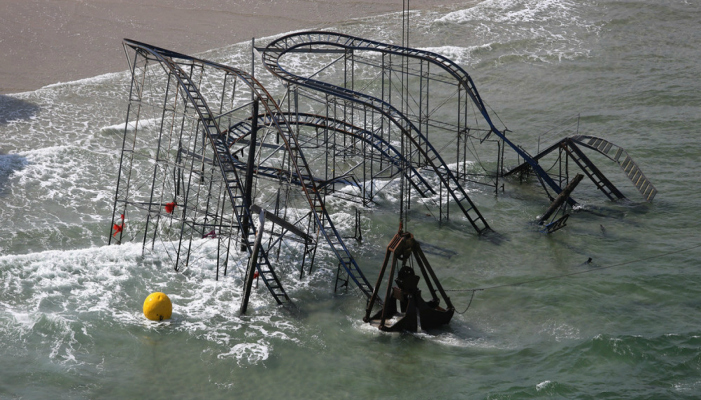 SEASIDE HEIGHTS, NJ - MAY 14:  A crane demolishes the JetStar roller coaster more than 6 months after it fell into the ocean during Superstorm Sandy on May 14, 2013 in Seaside Heights, New Jersey. The Casino Pier contracted Weeks Marine to remove the wreckage of the iconic roller coaster from the surf.  (Photo by John Moore/Getty Images.