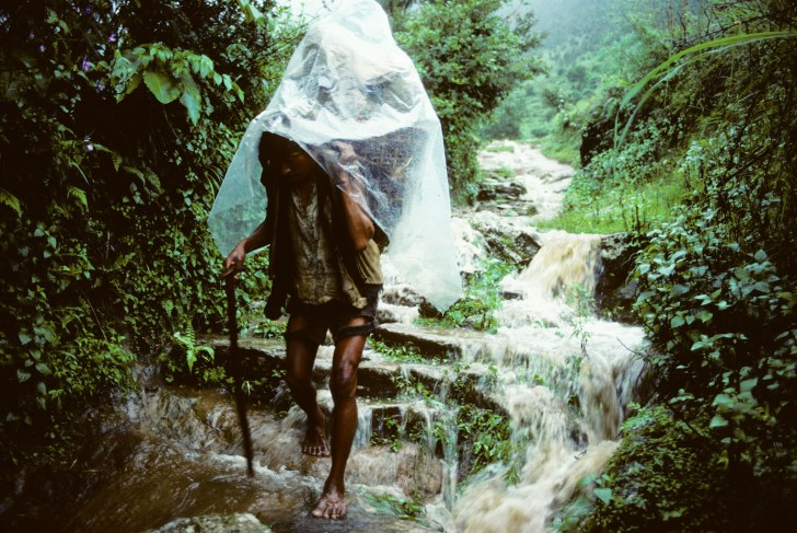 Lowland porter carries load through monsoon torrent on Canadian Mt Everest expedition. Nepal. 1982.