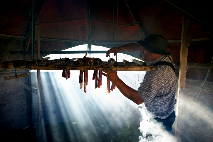 Fabian Byrd hangs the day's haul of Lake Trout in a traditional smoker at Drum Lake, the lodge he runs with his wife.