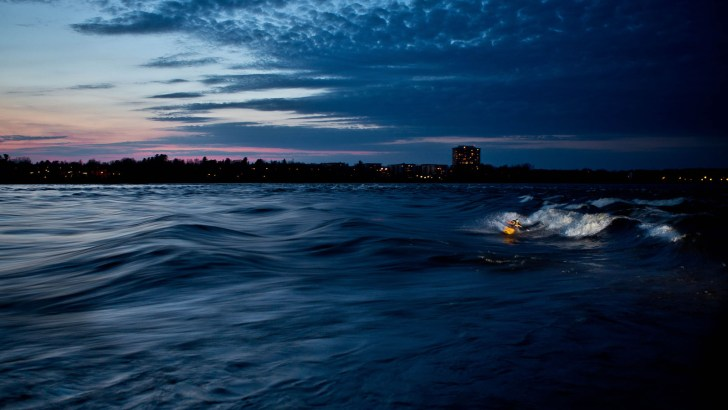 Andy Atkins gets a late evening kayak surf in at Champlain Bridge Rapids on the Ottawa River, Ottawa ON, Canada.