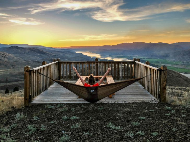 girl in hammock over looking sunset