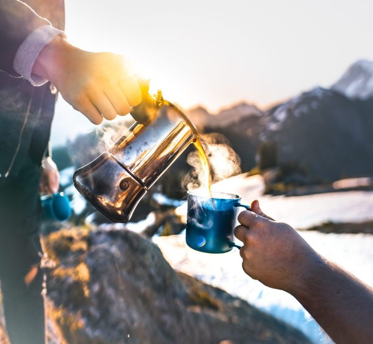 pouring coffee in the mountains at sunrise