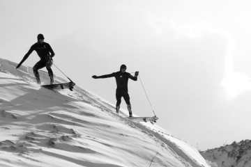 Pete Devries and Noah Cohen surfing on snow.