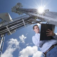 Wireless Towers and Man with Notebook