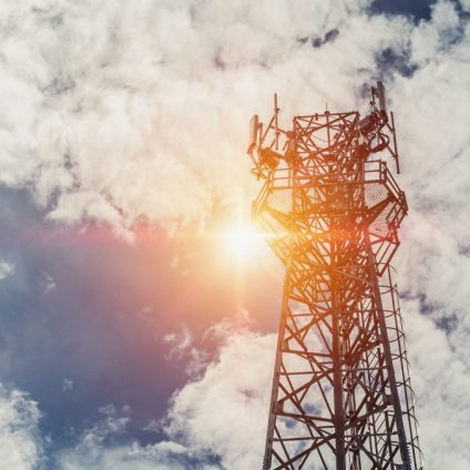 telecommunication tower with sun and blue sky