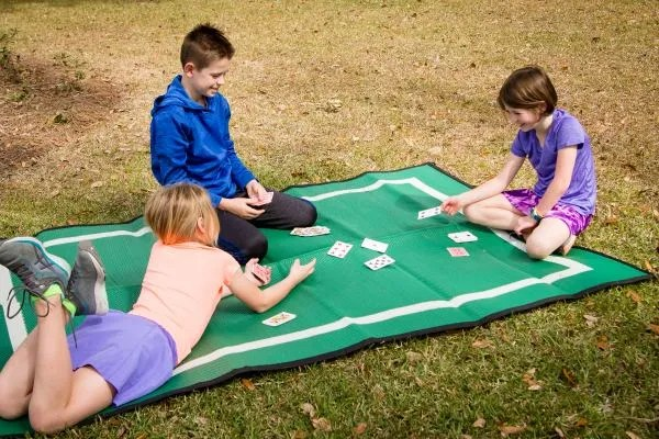 Three kids playing cards on outdoor playmat