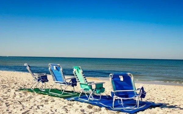 four beach chairs sitting on beach mats