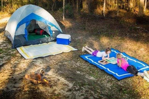 two girls playing at a campsite with tent and mountain mat