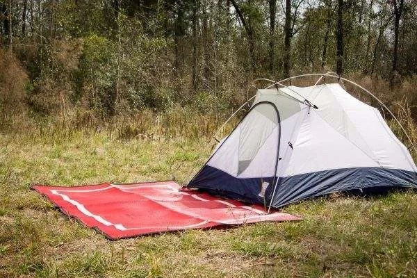 gray tent with red camping mat