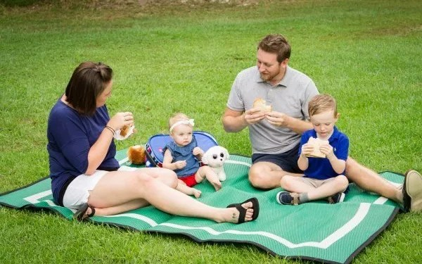 family having a picnic lunch on green Mountain Mat