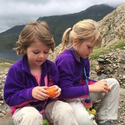 two little girls peeling oranges on hiking trail