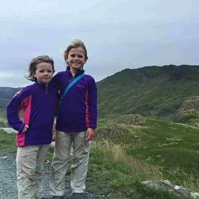 two girls standing on windy hiking trail